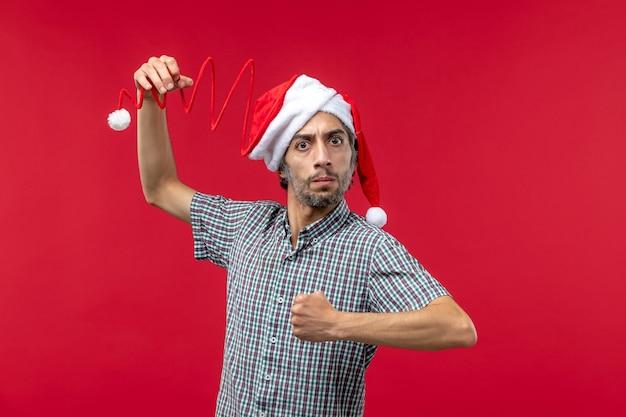 Widok z przodu młodego człowieka z gniewnym wyrazem na czerwonej ścianie