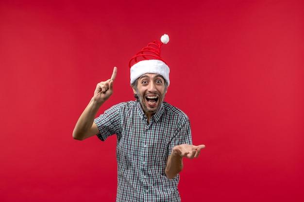 Widok z przodu młodego człowieka z podekscytowanym wyrazem na czerwonej ścianie