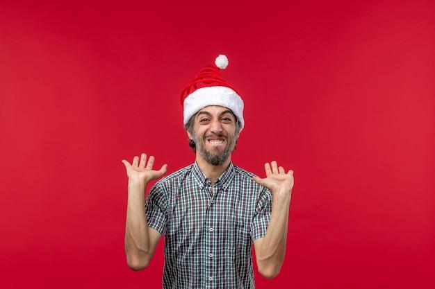 Widok z przodu młodego człowieka z podekscytowanym wyrazem na jasnoczerwonej ścianie