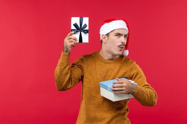 Widok z przodu młodego człowieka z prezentami na czerwonej ścianie