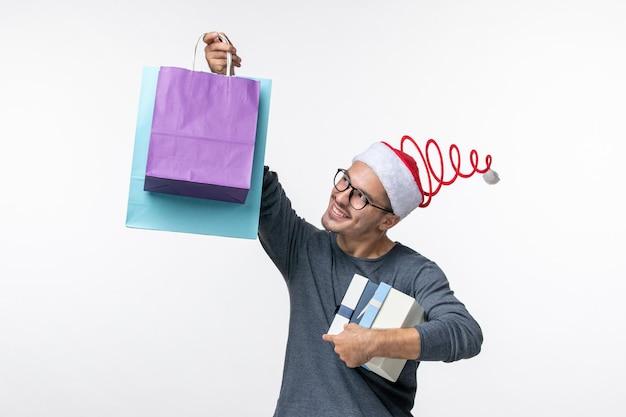 Widok z przodu młodego człowieka z prezentami świątecznymi na białej ścianie