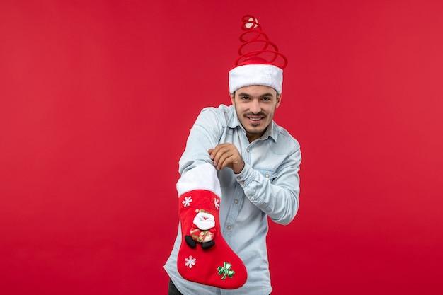 Widok z przodu młodego człowieka z skarpety świąteczne na czerwonej ścianie