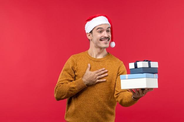 Widok z przodu młodego człowieka z uśmiechem na czerwonej ścianie