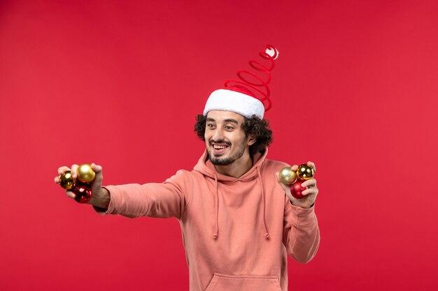 Widok z przodu młodego człowieka z zabawkami choinkowymi na czerwonej ścianie