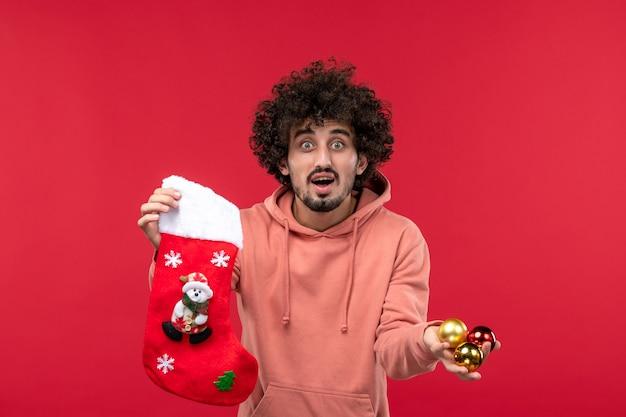 Widok z przodu młodego człowieka z zabawkami i skarpetą na czerwonej ścianie