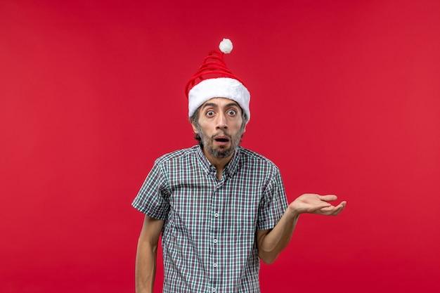 Widok z przodu młodego człowieka z zaskoczonym wyrazem na czerwonej ścianie