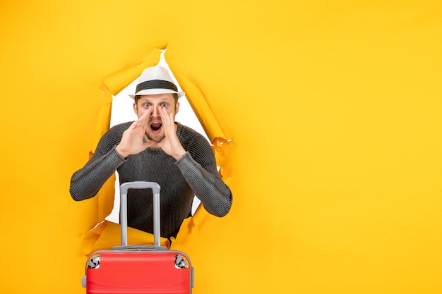 Widok z przodu młodego dorosłego trzymającego torbę i dzwoniącego do kogoś w rozdartej na żółtej ścianie