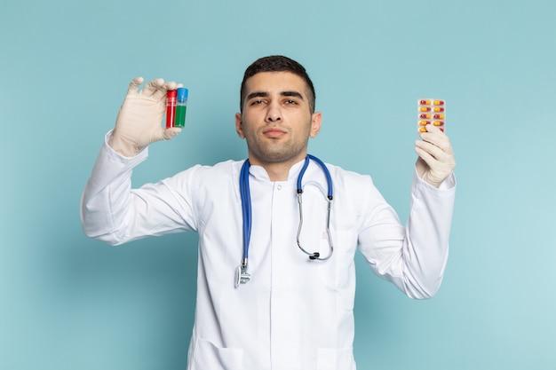 Widok z przodu młodego lekarza płci męskiej w białym garniturze z niebieskim stetoskopem trzymając kolby