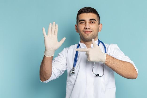 Widok z przodu młodego lekarza płci męskiej w białym garniturze z niebieskim stetoskopem, wskazując na rękawiczkę