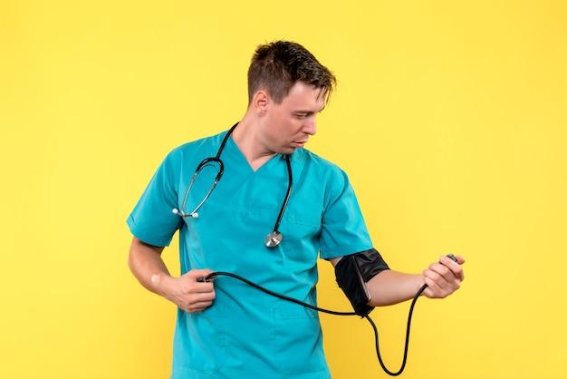 Widok z przodu młodego lekarza płci męskiej za pomocą tonometru na żółtej ścianie