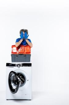 Widok z przodu młodego mechanika zakrywającego twarz pralką z rękami na białej ścianie