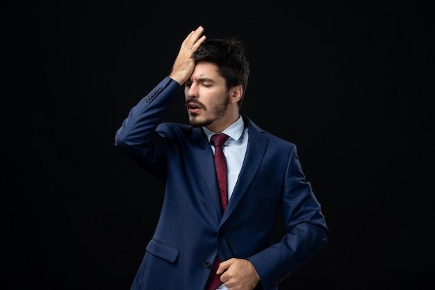 Widok z przodu młodego mężczyzny cierpiącego na ból głowy na izolowanej ciemnej ścianie