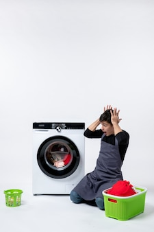 Widok z przodu młodego mężczyzny czekającego do końca prania ubrań na białej ścianie