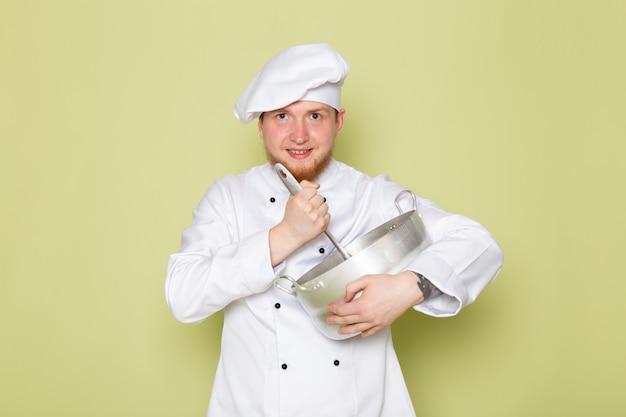 Widok z przodu młodego mężczyzny gotować w białym garniturze gotować białą czapkę głowy gospodarstwa srebrny rondel mieszania