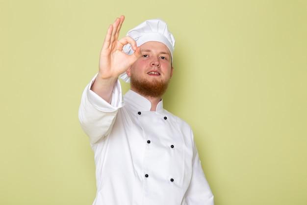 Widok z przodu młodego mężczyzny gotować w białym garniturze gotować białą czapkę głowy pokazano znak w porządku