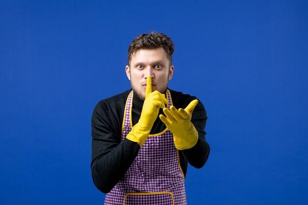 Widok z przodu młodego mężczyzny, który robi znak shh stojący na niebieskiej ścianie