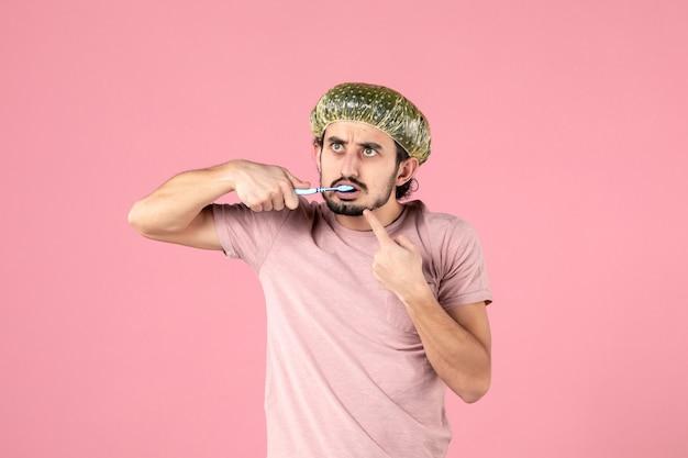 Widok z przodu młodego mężczyzny myjącego zęby na różowej ścianie