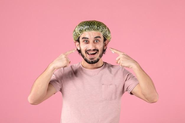 Widok z przodu młodego mężczyzny nakładającego maskę na twarz na różowej ścianie