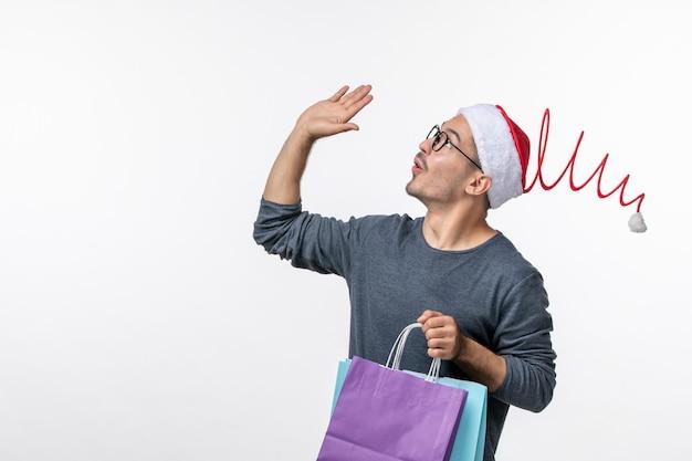 Widok z przodu młodego mężczyzny po świątecznych zakupach na białej ścianie