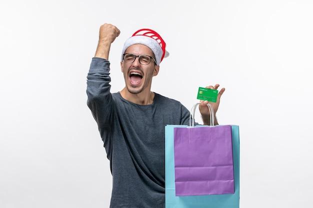Widok z przodu młodego mężczyzny po zakupach, radości na białej ścianie