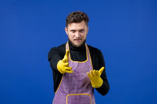 Widok z przodu młodego mężczyzny podającego rękę stojącego na niebieskiej ścianie