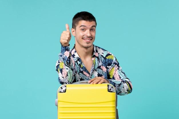 Widok z przodu młodego mężczyzny przygotowującego się do podróży z jego żółtą torbą na jasnoniebieskiej ścianie