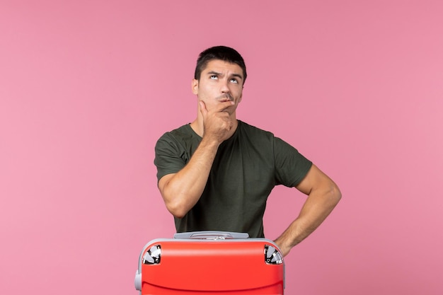 Widok z przodu młodego mężczyzny przygotowującego się do wakacji i myślącego o czymś na różowej przestrzeni