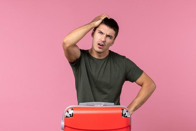 Widok z przodu młodego mężczyzny przygotowującego się do wakacji i myślącego o różowej przestrzeni