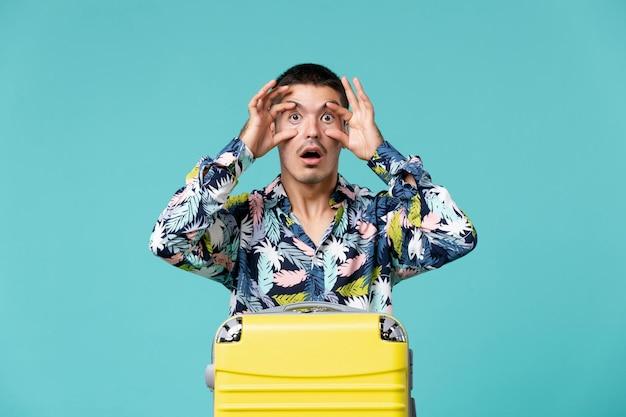 Widok z przodu młodego mężczyzny przygotowuje się do wakacji z torbą pozowanie na jasnoniebieskiej ścianie