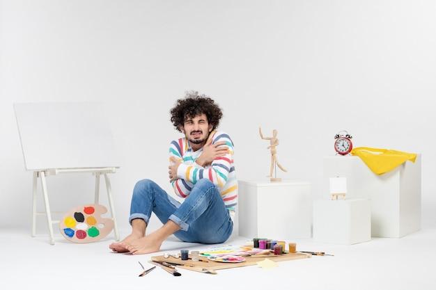 Widok z przodu młodego mężczyzny siedzącego wokół farb i rysunków na białej ścianie