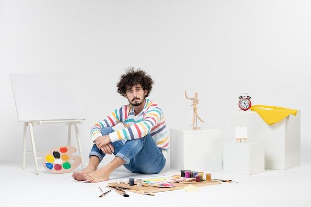 Widok z przodu młodego mężczyzny siedzącego wokół farb i rysunków znudzonych na białej ścianie