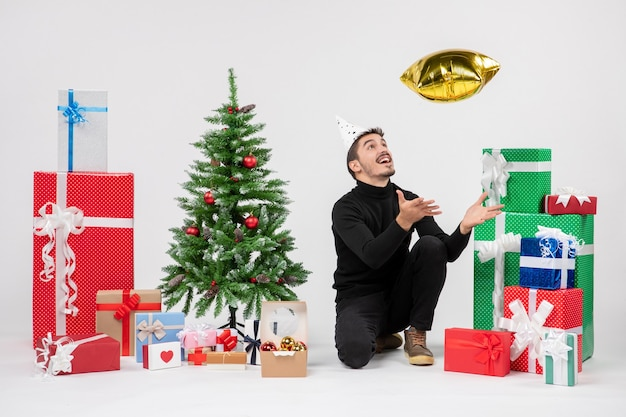 Widok z przodu młodego mężczyzny siedzącego wokół prezentów i rzucającego figurkę złotej gwiazdy na białej ścianie