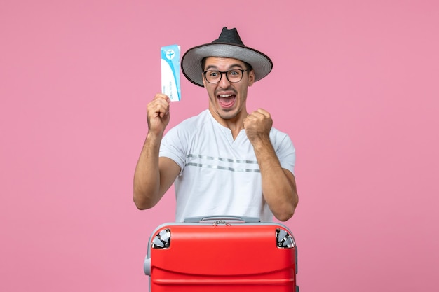 Widok z przodu młodego mężczyzny trzymającego bilet lotniczy na wakacje na jasnoróżowej ścianie