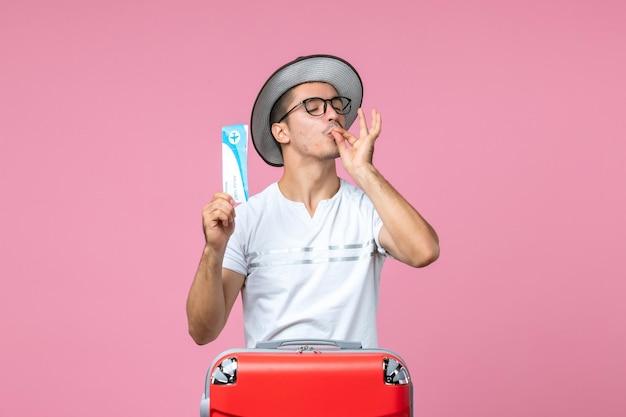 Widok z przodu młodego mężczyzny trzymającego bilet lotniczy na wakacje na różowej ścianie