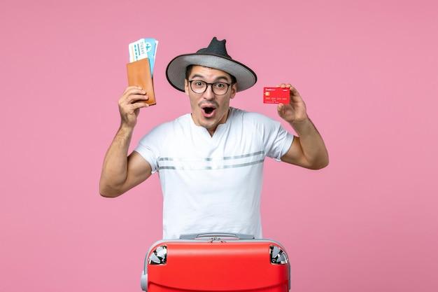 Widok z przodu młodego mężczyzny trzymającego bilety i kartę bankową na jasnoróżowej ścianie