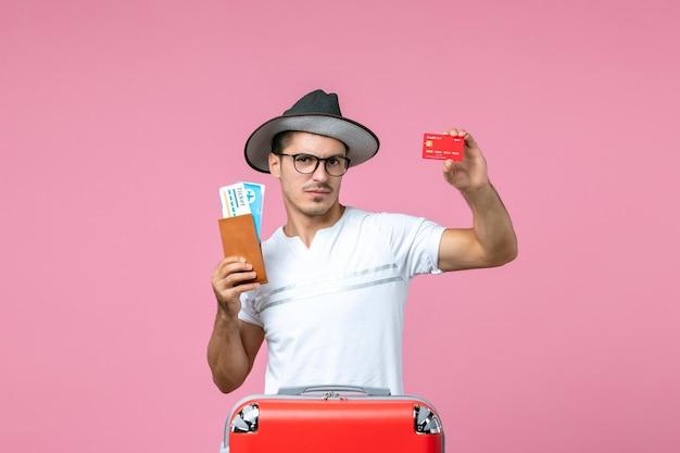 Widok z przodu młodego mężczyzny trzymającego bilety i kartę bankową na różowej ścianie