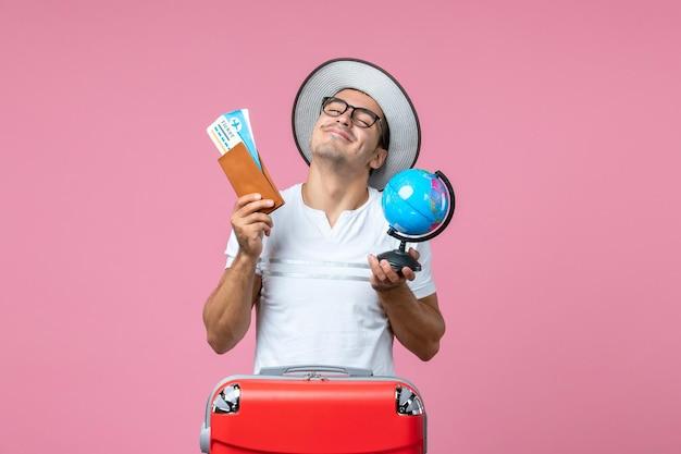 Widok z przodu młodego mężczyzny trzymającego bilety i małą kulę ziemską na różowej ścianie
