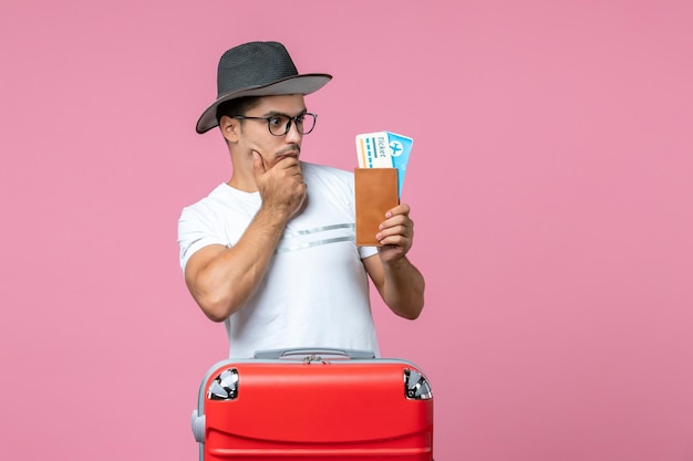 Widok z przodu młodego mężczyzny trzymającego bilety lotnicze przygotowujące się do wakacji na różowej ścianie