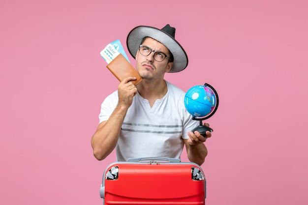 Widok z przodu młodego mężczyzny trzymającego bilety wakacyjne i małą kulę ziemską na różowej ścianie