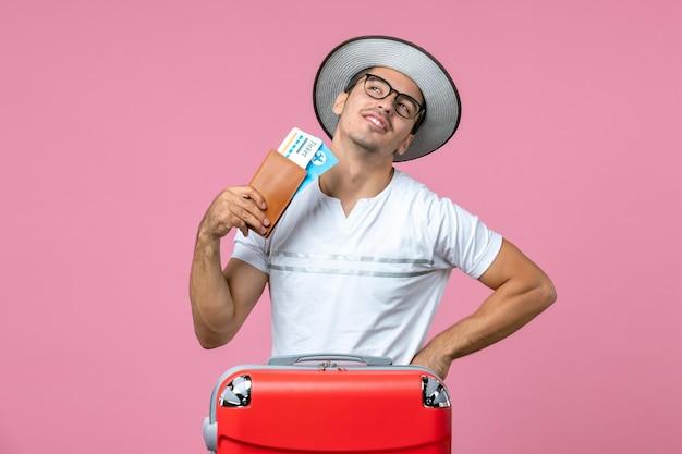 Widok z przodu młodego mężczyzny trzymającego bilety wakacyjne na różowej podłodze mężczyzna wakacje zdjęcie podróż samolotem podróż