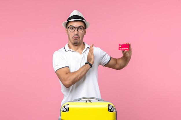 Widok z przodu młodego mężczyzny trzymającego czerwoną kartę bankową na letnie wakacje na różowej ścianie