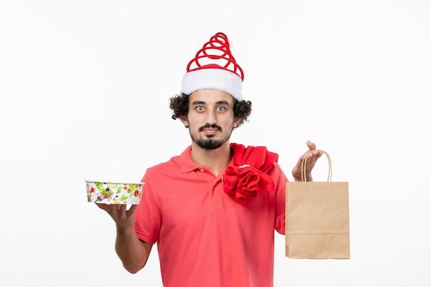 Widok z przodu młodego mężczyzny trzymającego dostawę jedzenia na białej ścianie