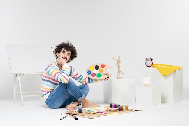 Widok z przodu młodego mężczyzny trzymającego farby i frędzle do rysowania na białej ścianie