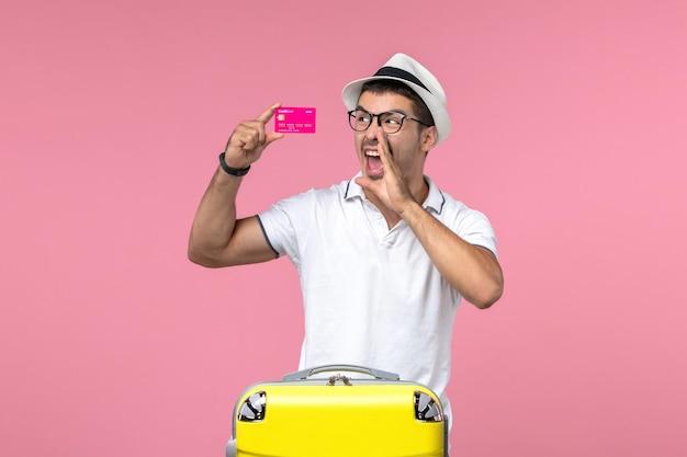 Widok z przodu młodego mężczyzny trzymającego kartę bankową na letnie wakacje na jasnoróżowej ścianie