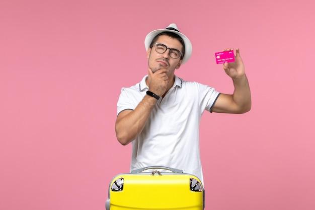 Widok z przodu młodego mężczyzny trzymającego kartę bankową na letnie wakacje na różowej ścianie