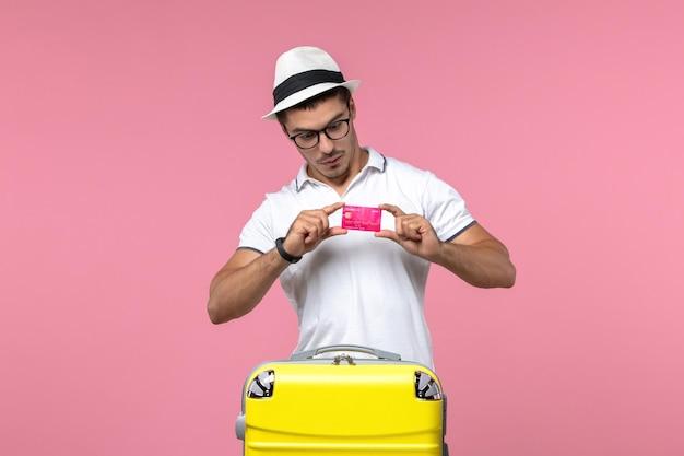 Widok z przodu młodego mężczyzny trzymającego kartę bankową na wakacjach na różowej ścianie