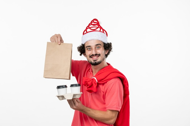 Widok z przodu młodego mężczyzny trzymającego kawę dostawy na białej ścianie