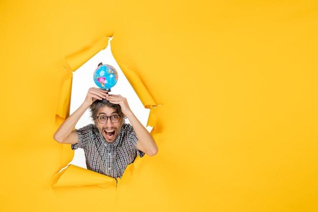 Widok z przodu młodego mężczyzny trzymającego kulę ziemską na żółtej ścianie