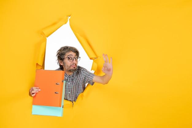 Widok z przodu młodego mężczyzny trzymającego pliki na żółtej ścianie