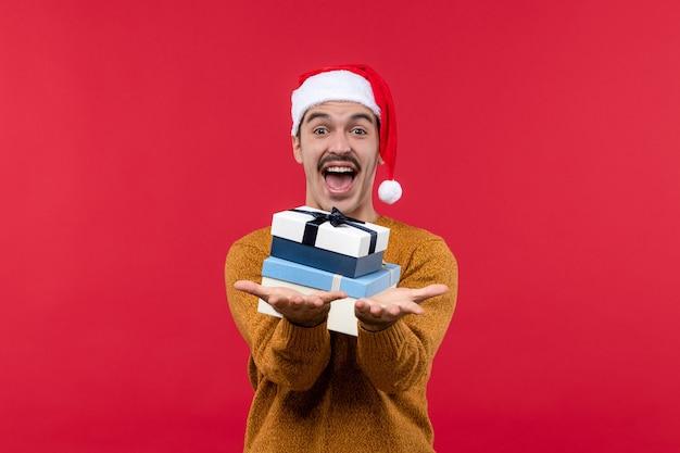 Widok z przodu młodego mężczyzny trzymającego prezenty na czerwonej ścianie